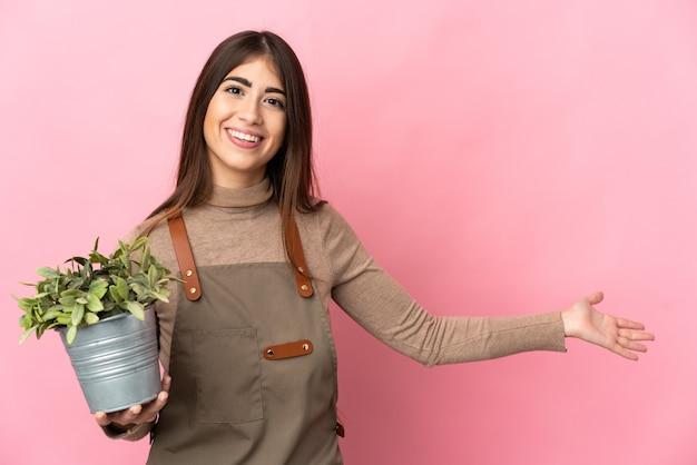 핑크 벽에 고립 된 식물을 들고 젊은 정원사 여자와 서 초대하기 위해 손을 옆으로 확장