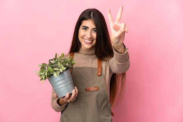 웃 고 승리 기호를 보여주는 분홍색 벽에 고립 된 식물을 들고 젊은 정원사 여자