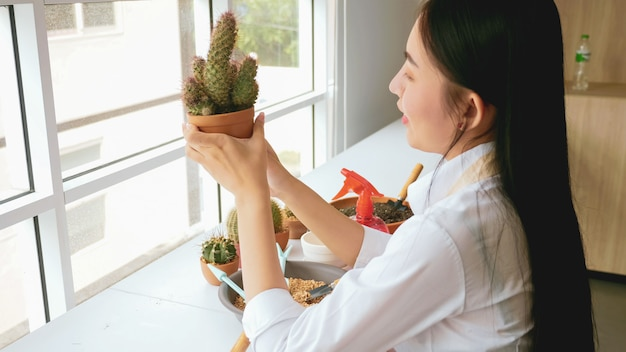 Young gardener woman holding a flowerpot of cactus in the room.