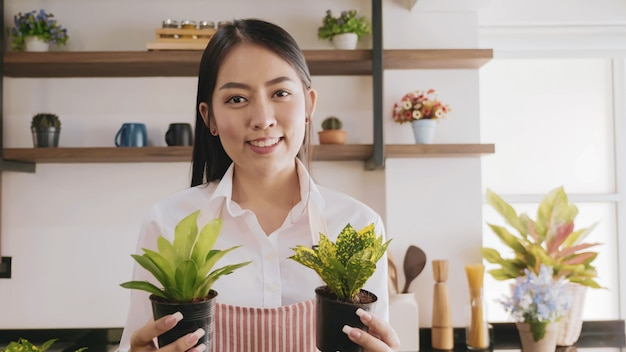 Young gardener woman holding flowerpot in the room.