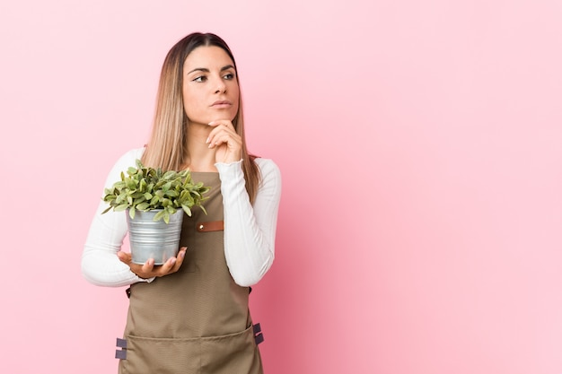 Young gardener woman holding a plant looking sideways with doubtful and skeptical expression.