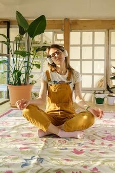 젊은 정원사 여성은 점프수트를 입은 아름다운 여성을 명상하고 헤드폰은 공부나 직장에서 휴식을 취합니다
