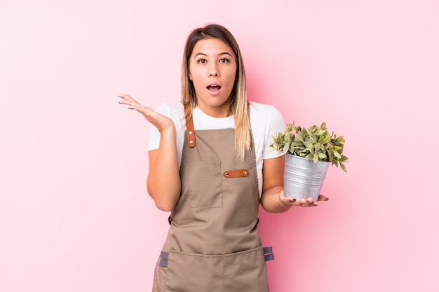 Young gardener woman surprised and shocked