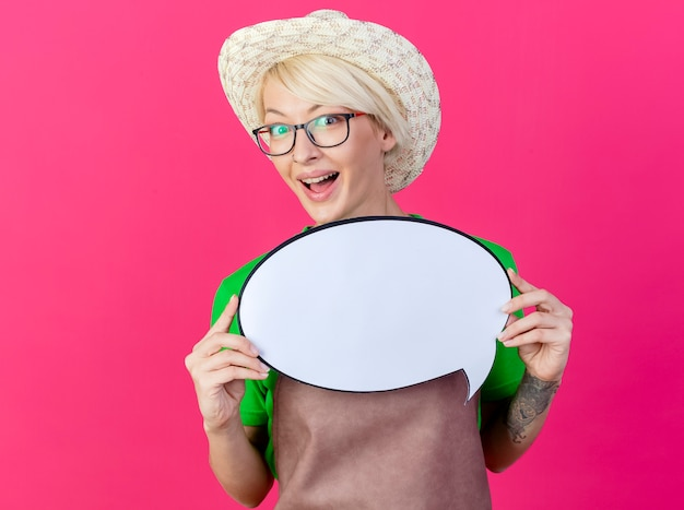Young gardener woman with short hair in apron and hat holding blank speech bubble sign looking at camera smiling with happy face standing over pink background