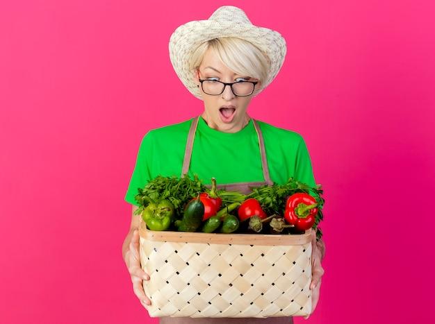 Giovane giardiniere donna con i capelli corti in grembiule e cappello tenendo la cassa piena di verdure