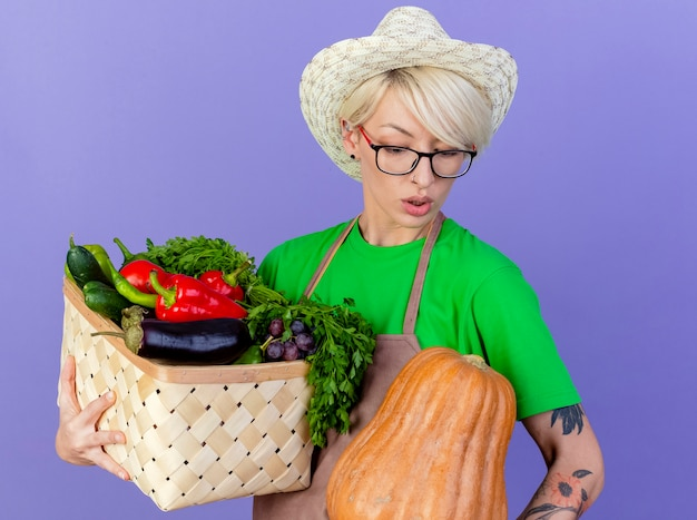 Young gardener woman with short hair in apron and hat holding crate full of vegetables