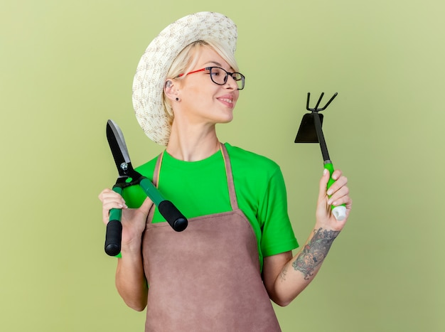 Young gardener woman with short hair in apron and hat holding gardening equipments looking aside with smile on happy face standing over light background