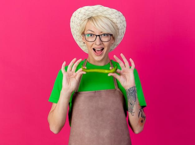 Giovane donna giardiniere con i capelli corti in grembiule e cappello che tiene peperoncino verde
