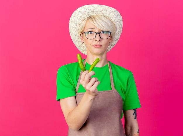 Giovane donna giardiniere con i capelli corti in grembiule e cappello che tiene metà del peperoncino verde