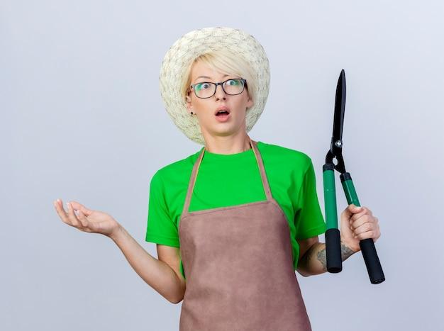 Giovane donna giardiniere con i capelli corti in grembiule e cappello che tiene in mano un tagliasiepi sorpreso e confuso che allarga il braccio di lato