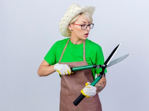 Giovane donna giardiniere con i capelli corti in grembiule e cappello che tiene tagliasiepi guardandola sorpresa looking