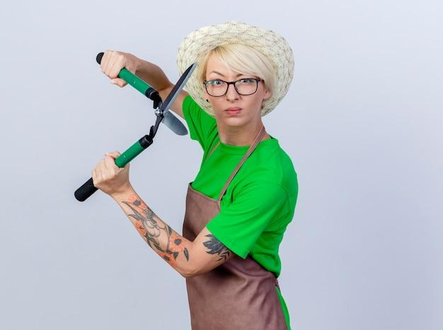 Giovane donna giardiniere con i capelli corti in grembiule e cappello che tiene tagliasiepi con faccia seria