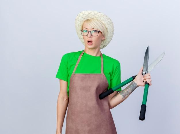 Giovane donna giardiniere con i capelli corti in grembiule e cappello che tiene tagliasiepi preoccupata