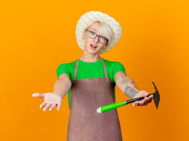 Giovane giardiniere donna con i capelli corti in grembiule e cappello azienda mattock guardando la telecamera con le braccia fuori come chiedere in piedi su sfondo arancione