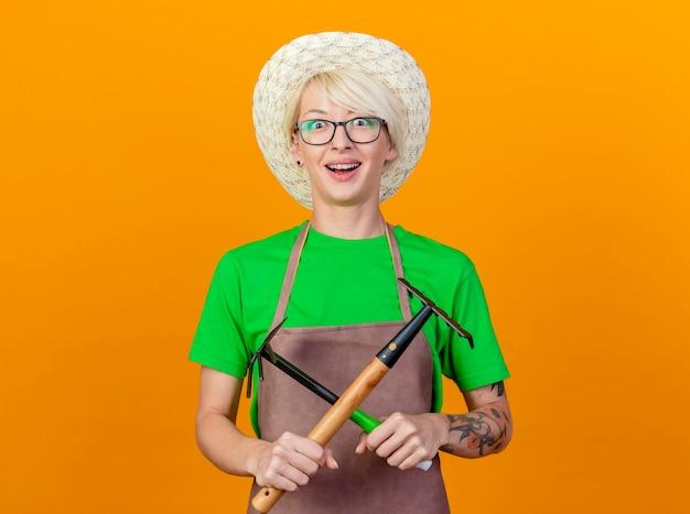 Giovane giardiniere donna con i capelli corti in grembiule e cappello azienda mattock e mini rastrello attraversando le mani sorridendo allegramente in piedi su sfondo arancione
