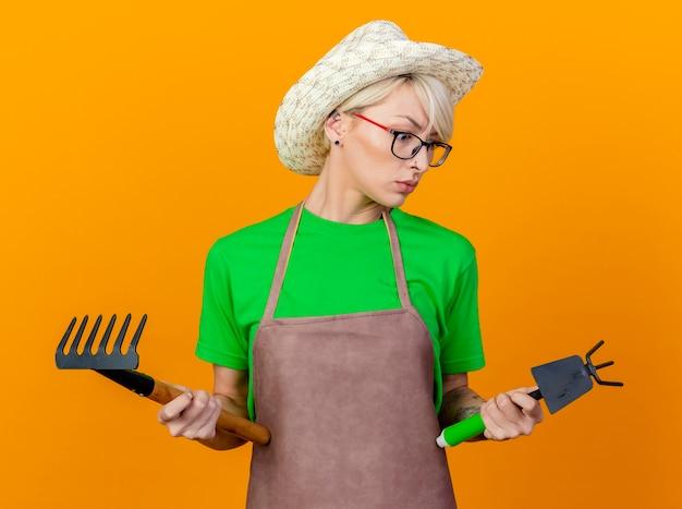 Giovane giardiniere donna con i capelli corti in grembiule e cappello azienda mattock e mini rastrello cercando confuso cercando di fare una scelta in piedi su sfondo arancione