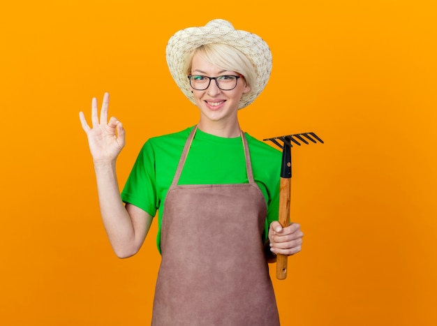 Giovane giardiniere donna con i capelli corti in grembiule e cappello azienda mini rastrello guardando la telecamera sorridente che mostra segno ok in piedi su sfondo arancione