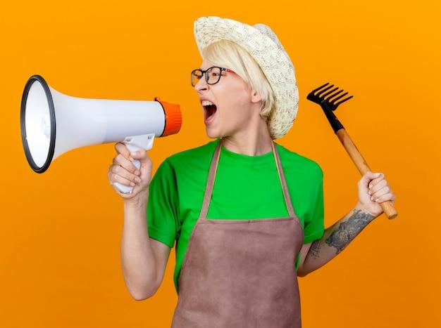 Giovane giardiniere donna con i capelli corti in grembiule e cappello tenendo mini rastrello che grida al megafono in piedi su sfondo arancione
