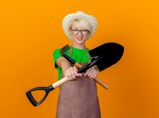 Young gardener woman with short hair in apron and hat holding mini rake and shovel looking at camera crossing hands smiling standing over orange background