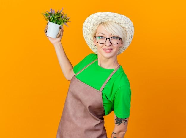 Giovane giardiniere donna con i capelli corti in grembiule e cappello azienda pianta in vaso guardando la telecamera sorridente con la faccia felice in piedi su sfondo arancione