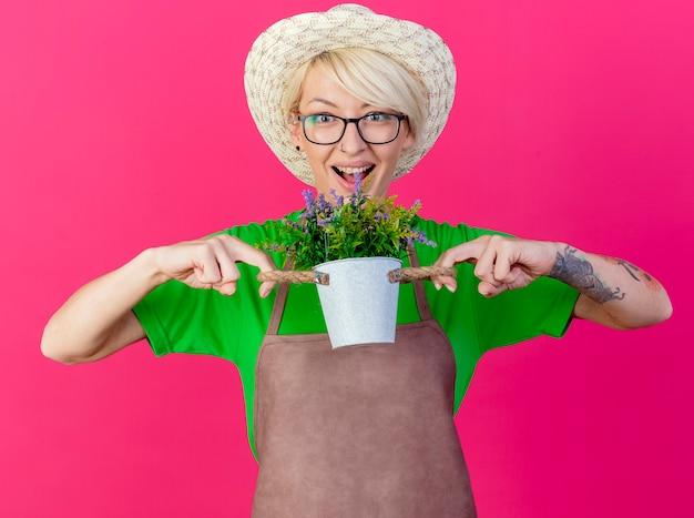 Giovane donna giardiniere con i capelli corti in grembiule e cappello che tiene pianta in vaso