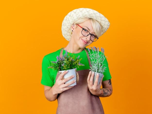 Giovane giardiniere donna con i capelli corti in grembiule e cappello azienda piante in vaso guardando la telecamera sorridente con la faccia felice in piedi su sfondo arancione