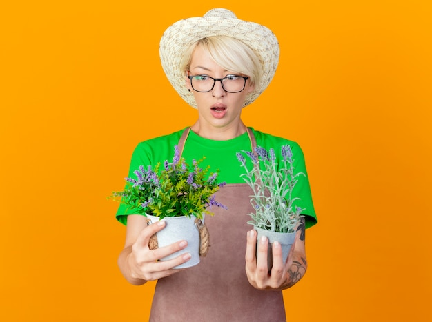 Giovane giardiniere donna con i capelli corti in grembiule e cappello tenendo le piante in vaso guardandole confuse cercando di fare una scelta in piedi su sfondo arancione