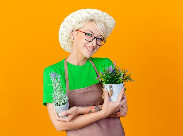Giovane giardiniere donna con i capelli corti in grembiule e cappello azienda piante in vaso sorridente con faccia felice guardando la telecamera in piedi su sfondo arancione