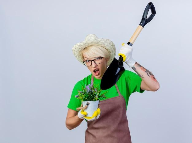 Giovane donna giardiniere con i capelli corti in grembiule e cappello che tiene la pala e la pianta in vaso confusa