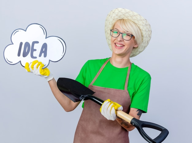 Young gardener woman with short hair in apron and hat holding shovel showing speech buble sign with word idea smiling with happy face