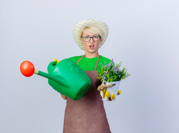 Young gardener woman with short hair in apron and hat holding watering can and potted plant being confused and displeased