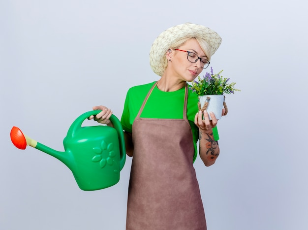 Young gardener woman with short hair in apron and hat holding watering can and potted plant feeling pleasant aroma