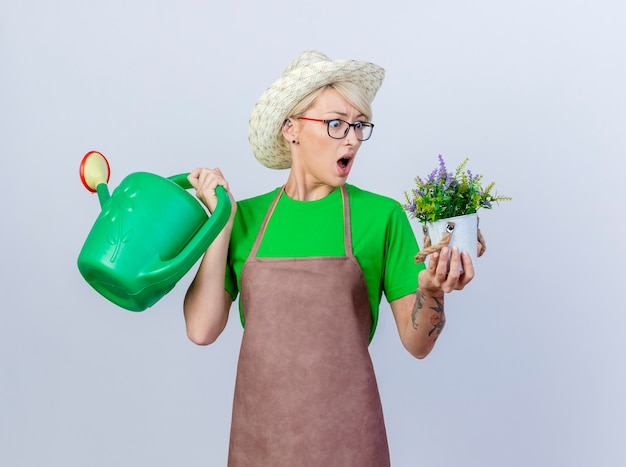 Young gardener woman with short hair in apron and hat holding watering can and potted plant looking at plant being surprised