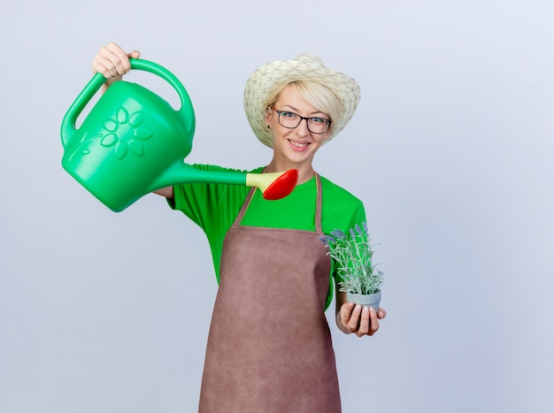 Young gardener woman with short hair in apron and hat holding watering can and potted plant smiling with happy face