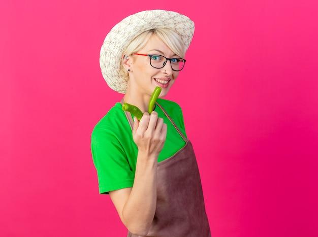 Giovane donna giardiniere con i capelli corti in grembiule e cappello che mostra le metà del peperoncino verde
