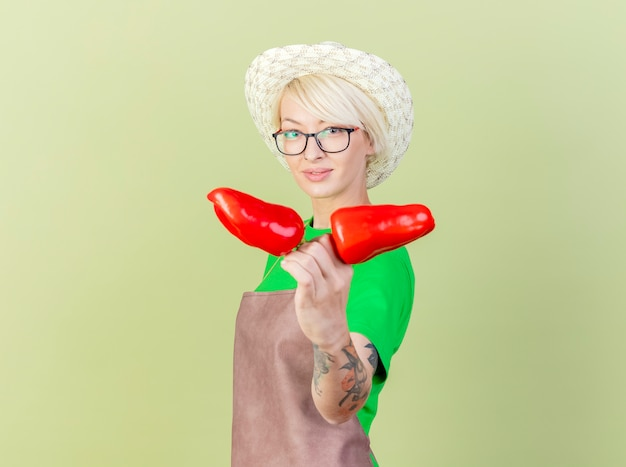Young gardener woman with short hair in apron and hat showing red bell peppers  with smile on face