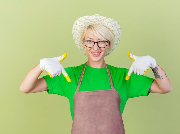 Giovane giardiniere donna con i capelli corti in grembiule e cappello che indossa guanti di gomma rivolti con le dita indice verso il basso sorridendo allegramente in piedi su sfondo chiaro
