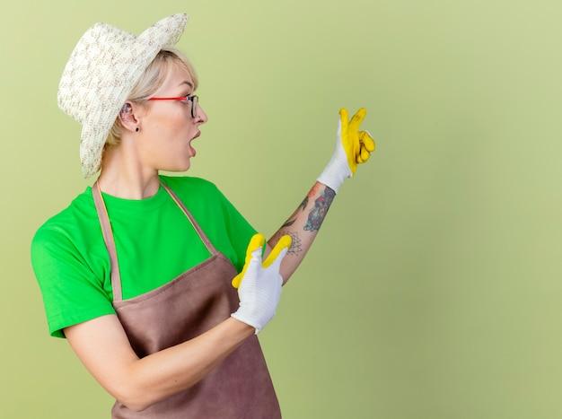 Giovane giardiniere donna con i capelli corti in grembiule e cappello che indossa guanti di gomma che punta con il dito indice a qualcosa indietro guardando sorpreso in piedi su sfondo chiaro