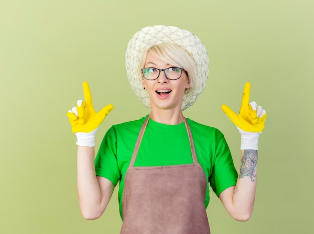 Giovane giardiniere donna con i capelli corti in grembiule e cappello che indossa guanti di gomma rivolti con le dita indice fino a sorridere allegramente in piedi su sfondo chiaro