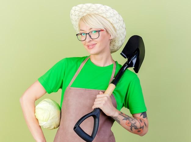 エプロンと帽子の短い髪の若い庭師の女性は、明るい背景の上に立って幸せそうな顔で笑顔のカメラを見てキャベツとシャベルを肩に保持しています
