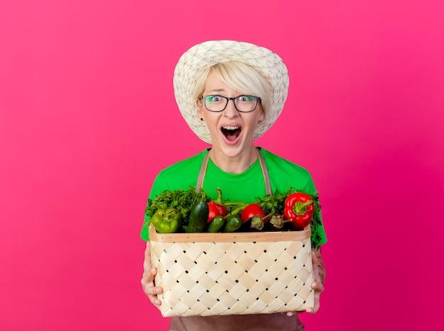 Молодая женщина-садовник с короткими волосами в фартуке и шляпе держит ящик, полный овощей