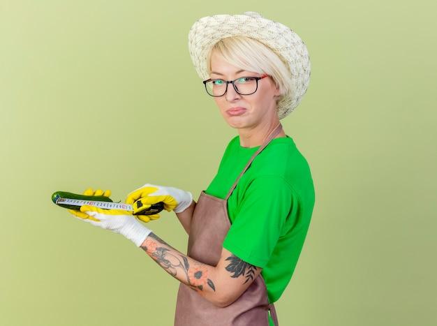 앞치마와 모자에 짧은 머리를 가진 젊은 정원사 여자는 밝은 배경 위에 서 혼란 스 러 워 카메라를보고 측정 테이프로 그것을 측정하는 가지를 들고