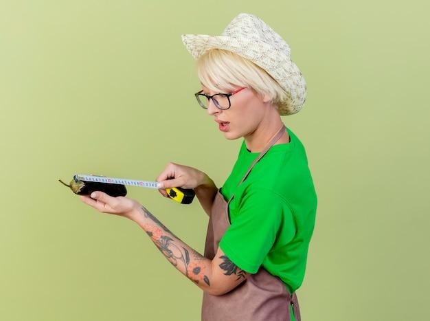 앞치마와 모자에 짧은 머리를 가진 젊은 정원사 여자 밝은 배경 위에 자신감이 서 찾고 측정 테이프로 측정 가지를 들고