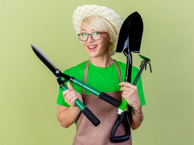 Молодая женщина-садовник с короткими волосами в фартуке и шляпе, держащая садовое оборудование, смотрит в камеру с улыбкой на счастливом лице, стоящем на светлом фоне Бесплатные Фотографии