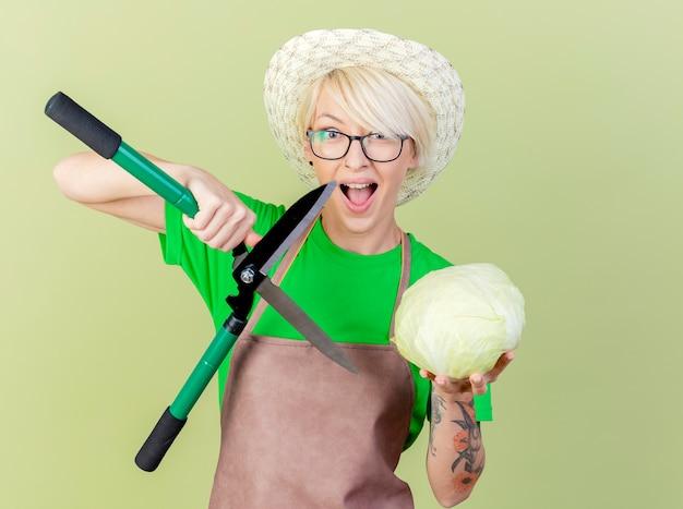 エプロンと帽子の短い髪の若い庭師の女性は、明るい背景の上に立って幸せで興奮してヘッジクリッパーとキャベツを保持しています