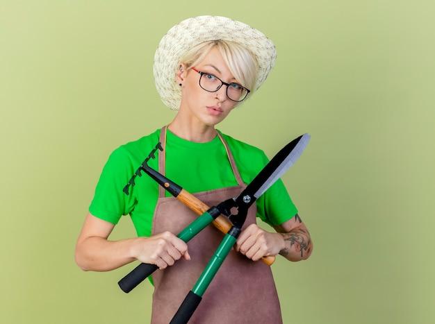 Молодая женщина-садовник с короткими волосами в фартуке и шляпе, держащая ножницы для живой изгороди и мини-грабли, смотрит в камеру с серьезным лицом, стоящим на светлом фоне