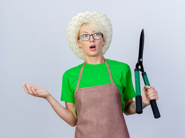 앞치마에 짧은 머리를 가진 젊은 정원사 여자와 헤지 클리퍼를 들고 모자는 옆으로 팔을 펼치고 혼란 스럽습니다.