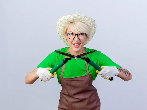 Молодая женщина-садовник с короткими волосами в фартуке и шляпе, весело улыбаясь, держит ножницы для живой изгороди