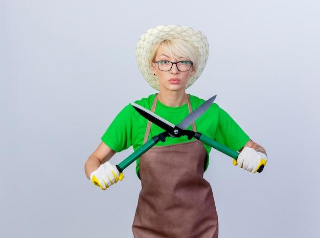 エプロンに短い髪の若い庭師の女性と真剣な顔でヘッジ クリッパーを保持している帽子
