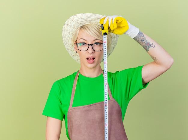 측정 테이프를 들고 앞치마와 모자에 짧은 머리를 가진 젊은 정원사 여자